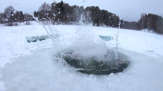 young man jumps into the ice hole - dziura filmów i materiałów b-roll