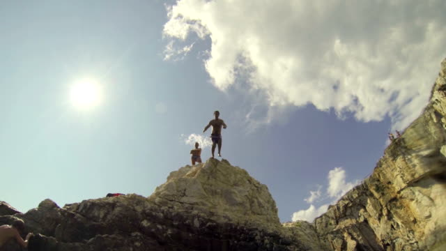 SLOW MOTION: Young man jumps into the ocean video