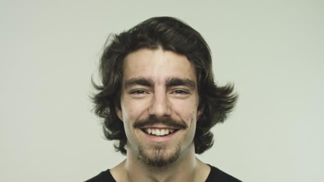 회색 배경에 대해 웃고 있는 젊은 남자 - 이를 드러낸 미소 스톡 비디오 및 b-롤 화면