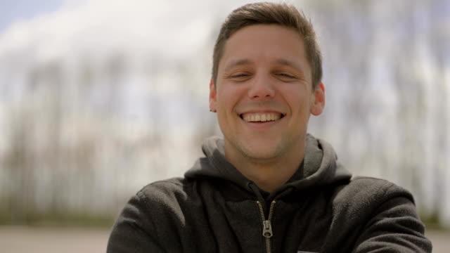 stockvideo's en b-roll-footage met jonge man lachen en kijken naar camera outdoor - portrait background
