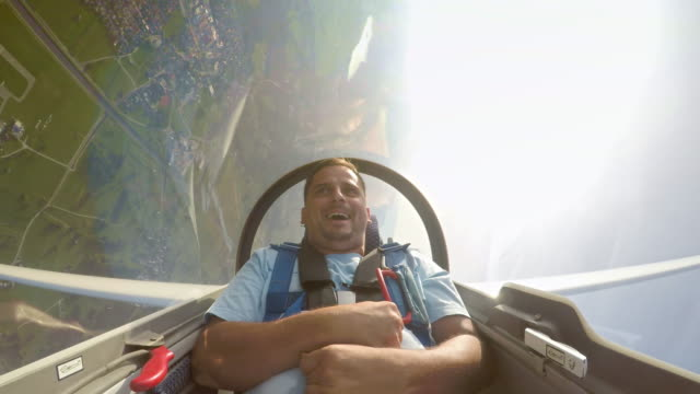 LD Young man laughing in the glider as it turns upside down in the sunny sky Wide locked down shot of a young man laughing in the sailplane as it turns upside down in the sunny sky. Shot in Slovenia. front view stock videos & royalty-free footage