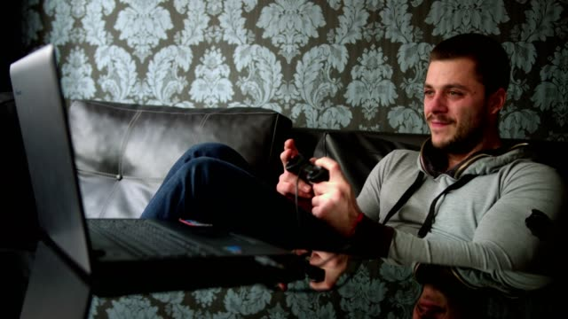 stockvideo's en b-roll-footage met jongeman tot op de bank thuis spelen van videogames op zijn laptop met een gamepad - vrijetijdsspel