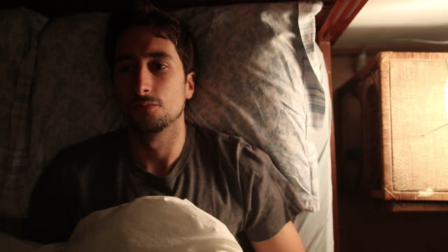 Young man lays down in bed, about to go to sleep, thinks about life for a brief moment in time, and then turns off the lamp from nightstand Young man lays down in bed, about to go to sleep, thinks about life for a brief moment in time, and then turns off the lamp from nightstand insomnia stock videos & royalty-free footage