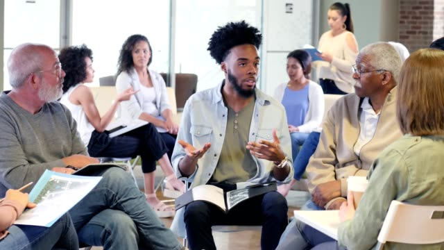 Young man leads multi-ethnic discussion group