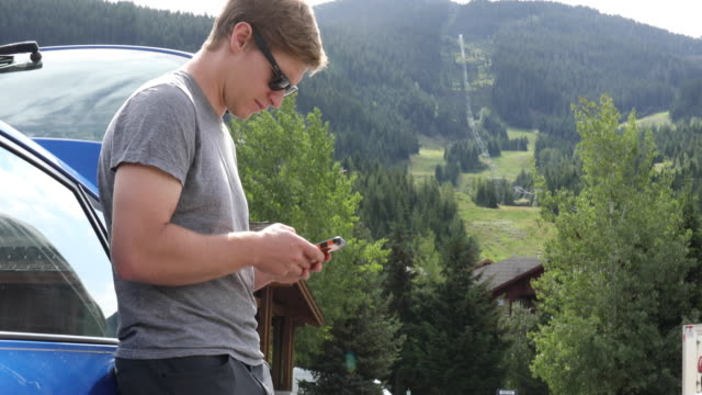 Young man leans against car while texting Bike bag and helmet visible, he looks off to distant scene towards bike park, Whistler, BC leaning stock videos & royalty-free footage