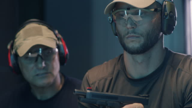 Young man learning to fire pistol with trainer