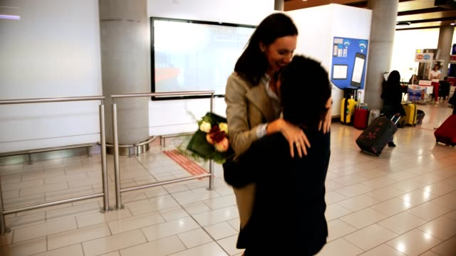 vidéos et rushes de jeune homme soulevant et en se félicitant de l'épouse à l'aéroport - femme seule s'enlacer