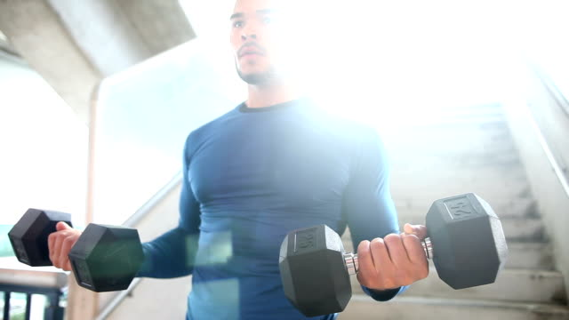 Young man lifting weights to strengthen biceps video