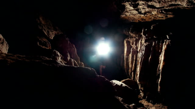 Young man lights the way with flashlight in dark cave for explorers group Young man lights the way with flashlight in dark cave for explorers group, close up cave stock videos & royalty-free footage