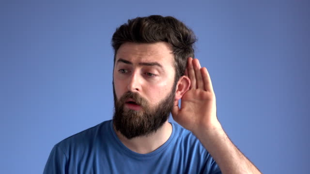 young man listening for gossip on blue background - curiosità video stock e b–roll