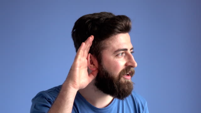 young man listening for gossip on blue background - orecchio umano video stock e b–roll