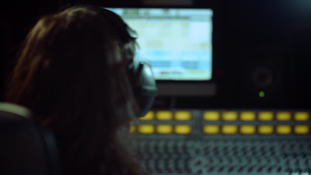 Young man listening music in recording studio. Composer turning to soundboard.