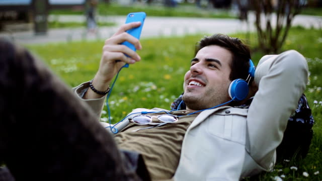 Young man listening music lying down outdoor video