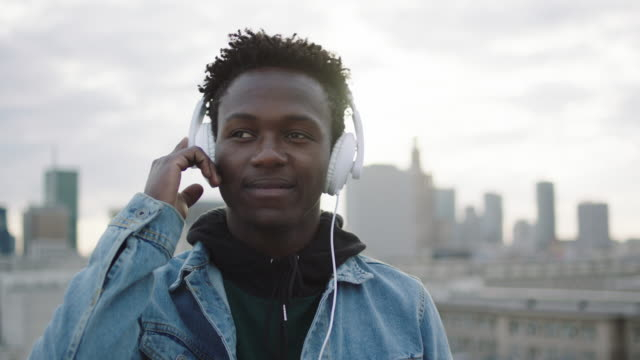 Young man listening music on roof. Holding hand on headphones video