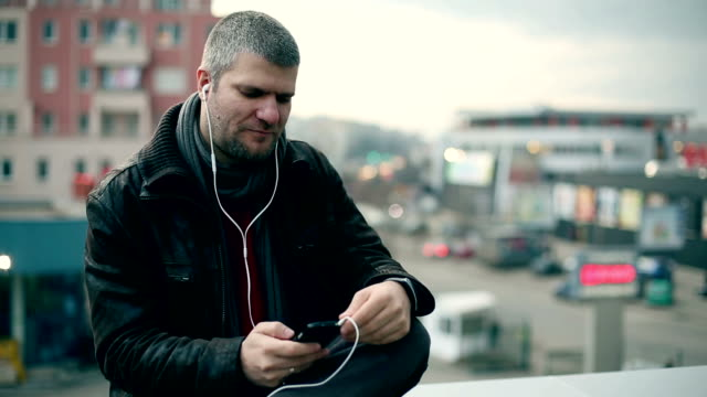 Young man listening music on the roof video