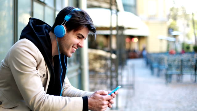 Young man listening music outdoor and texting video