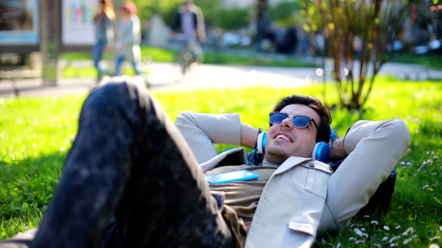 Young man listening music outdoor in the park video