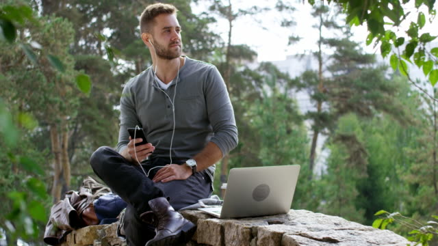 Young Man Listening to Music on Smartphone Tracking shot of young male freelancer in casual clothes sitting on stone bridge and listening to music with headphones and smartphone minority groups stock videos & royalty-free footage
