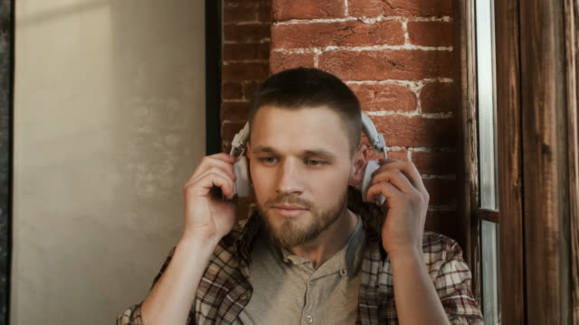 Young Man Listens To Music On Headphones. Man Sits On The Windowsill Near The Window. Close-up.