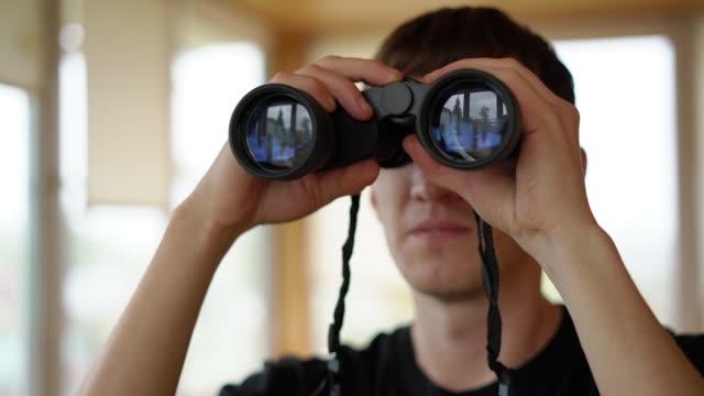 a young man look in the binoculars - google стоковые видео и кадры b-roll