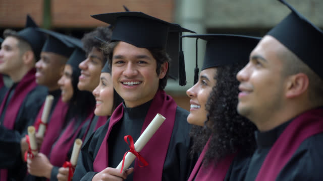 young man looking at camera during the graduation ceremony while peers stand in a row looking away - distrarre lo sguardo video stock e b–roll