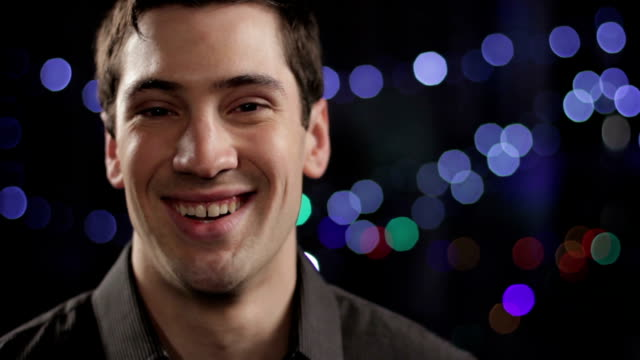 Young man looking at camera, smiling with lights in background video