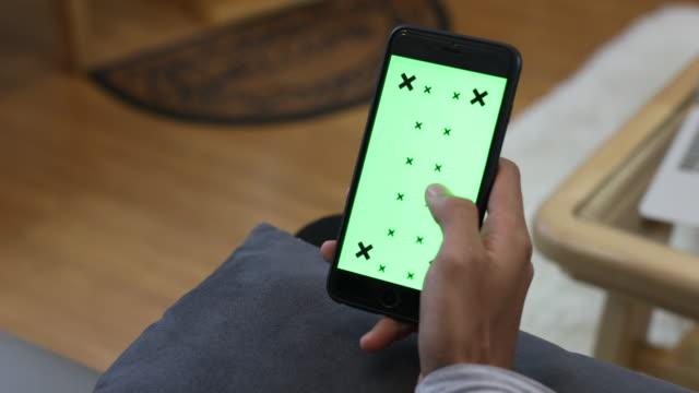 ung man tittar på smartphone med grön skärm - telefonmeddelande bildbanksvideor och videomaterial från bakom kulisserna