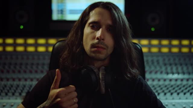 młody człowiek szuka kamery w studiu muzycznym. skoncentrowany męski muzyk cieszący się muzyką. - długie włosy filmów i materiałów b-roll