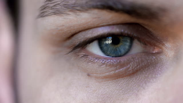 young man looking into the camera with his blue eye: close up video