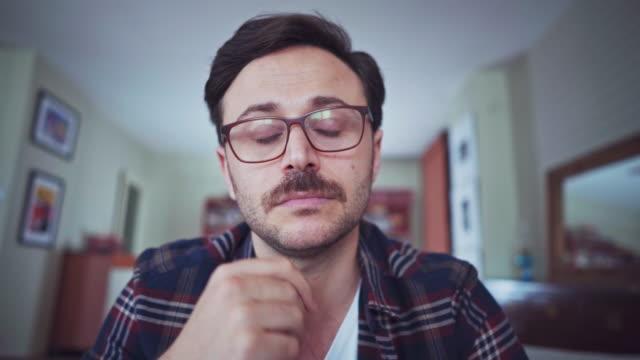 ung man som tittar på kamera och lyssna - listen bildbanksvideor och videomaterial från bakom kulisserna