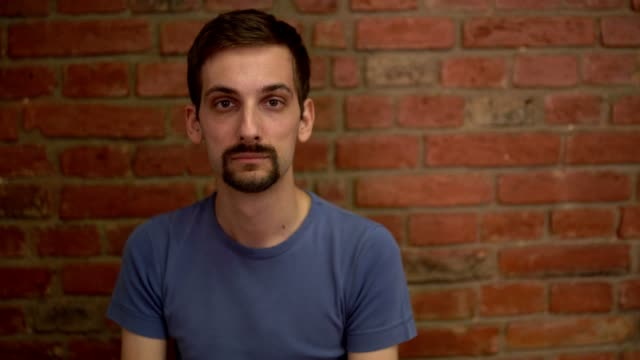 young man looks emotionless  while looking at the camera - miroslav mitic stock videos and b-roll footage