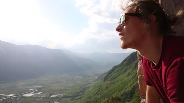 young man looks off to mountain view, from castle rampart - spektakularny krajobraz filmów i materiałów b-roll