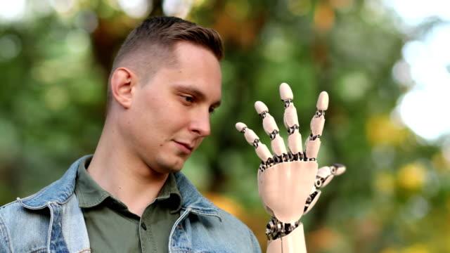 stockvideo's en b-roll-footage met jonge man kijkt op zijn robotic hand in het park - menselijke vinger