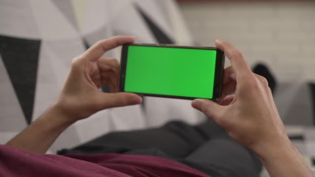 kanepede yatan genç adam onun cep telefonu, yeşil ekran bakarak - taşınabilirlik stok videoları ve detay görüntü çekimi