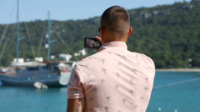 young man make panoramic photo or video with smartphone near sea beach - colore saturo video stock e b–roll