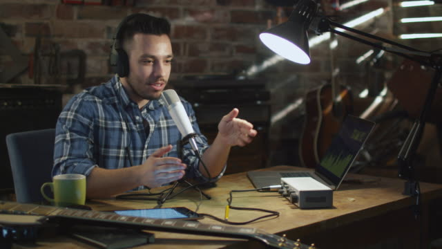 Young man makes a podcast audio recording at home in a garage. video
