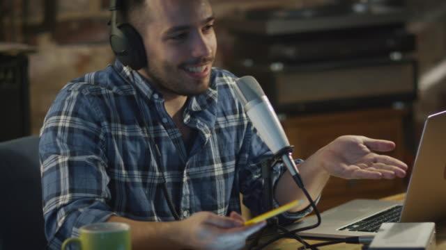 vídeos de stock, filmes e b-roll de jovem faz um podcast de áudio de gravação em casa em uma garagem. - podcast