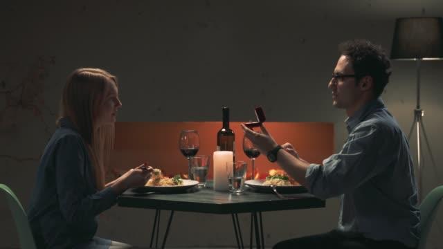 junger mann macht ein angebot der ehe um seine freundin - verlobung stock-videos und b-roll-filmmaterial