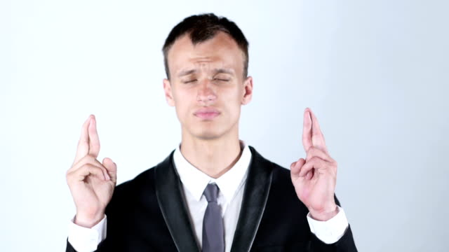 Young man making a wish with cross fingers video