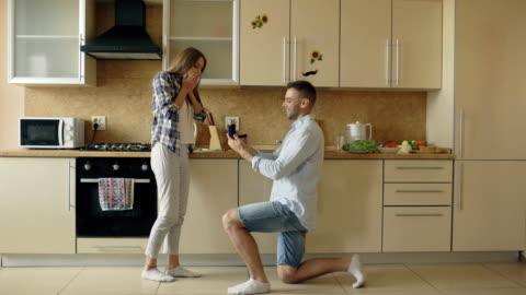 giovane che fa proposta alla sua ragazza in cucina a casa - fidanzato video stock e b–roll