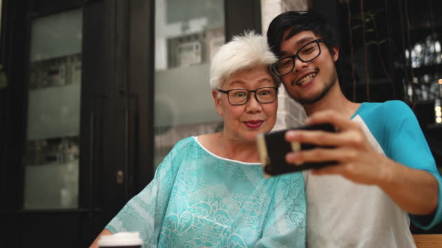 young man making selfie with his grandmother - grandparents stock videos & royalty-free footage