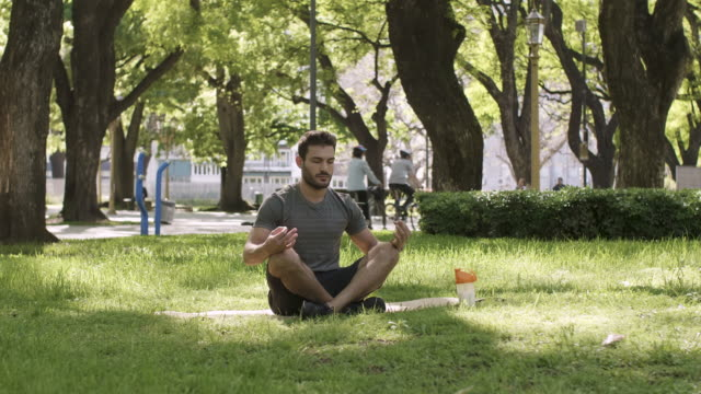 A young man meditating in urban park A latino male sitting on a yoga mat in a city park. Hands in a yoga position for meditation. A protein shake next to him. general view stock videos & royalty-free footage