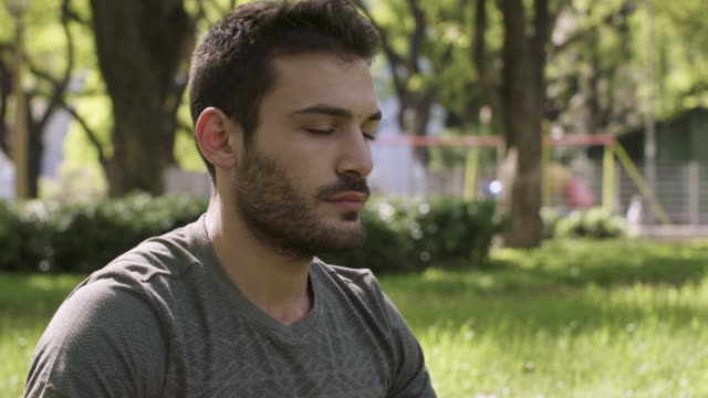 a young man meditating in urban park - mindfulness стоковые видео и кадры b-roll