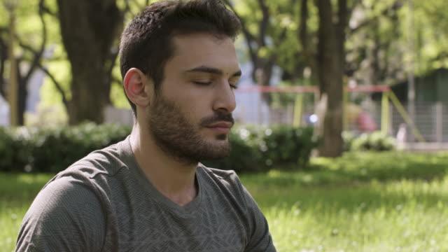 도시 공원에서 명상하는 청년 - mindfulness 스톡 비디오 및 b-롤 화면