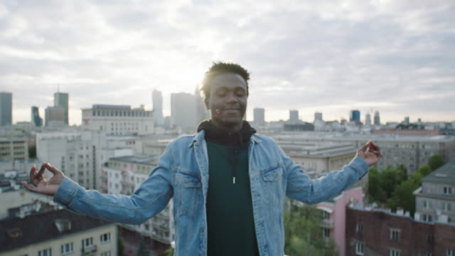Young man meditating on roof.  Cityscape in the background African man having closed eyes, meditating on the roof meditating stock videos & royalty-free footage