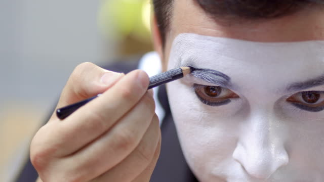Young man mime paint his eyebrows with black pencil video