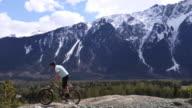 istock Young man mountain bikes along mountain ridge crest 1220185836