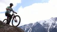 istock Young man mountain bikes along mountain ridge crest 1220186509