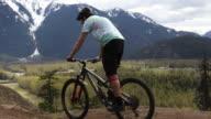 istock Young man mountain bikes along mountain ridge crest 1220193982