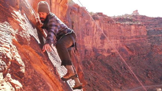 vídeos y material grabado en eventos de stock de joven escalador de montaña en moab - escalada en rocas